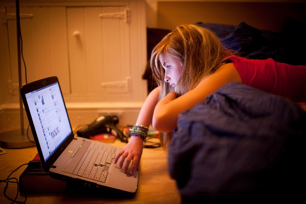 a  12 twelve 13 thirteen year old teenage girl on bed in her bedroom at night reading  Facebook page on laptop computer UK